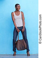 tall beautiful fashion woman smiling with bag