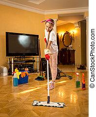 Full length portrait of teen girl washing wooden floor with ...