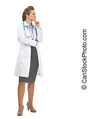 Full length portrait of thoughtful doctor woman looking on copy space
