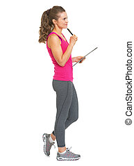 Full length portrait of thoughtful fitness trainer with clipboard