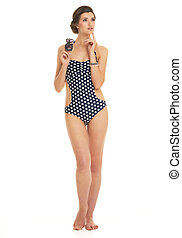 Full length portrait of thoughtful young woman in swimsuit