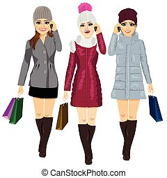 three young fashion women with shopping bags in winter clothes talking on the phone and walking forward