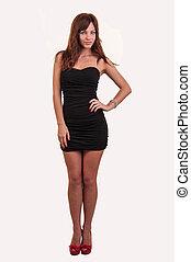 Full length portrait of trendy young woman in elegant black dress posing against white background