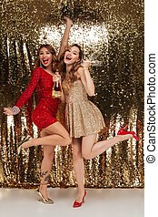 Full length portrait of two joyful girls in shiny dresses -...