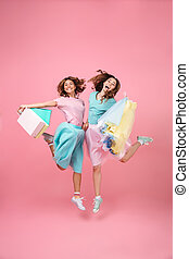 Full length portrait of two joyful pretty girls dressed in...