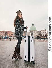 Full length portrait of woman with big luggage bag in Venice