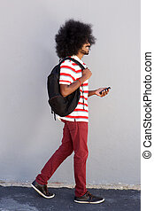 young black man walking with bag and mobile phone