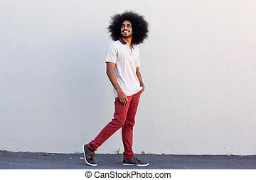 young man smiling and walking by white wall