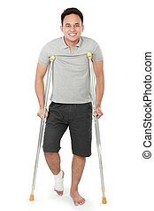 young man with broken leg use crutches - full length...