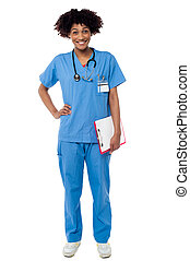 Charming female doctor with clipboard in hand, full length studio shot.