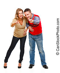 Full length portrait of young pregnant woman with husband pointing in camera on white background