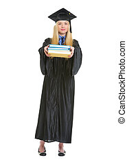 Full length portrait of young woman in graduation gown giving books