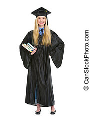 Full length portrait of young woman in graduation gown with books