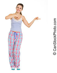 Full length portrait of young woman in pajamas pointing on copy space