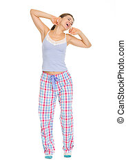 Full length portrait of young woman in pajamas stretching...