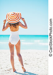 Full length portrait of young woman on beach. rear view