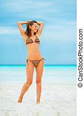 Full length portrait of young woman relaxing on beach