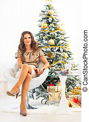 Full length portrait of young woman sitting near christmas tree