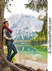 Full length portrait of young woman standing near tree on lake b