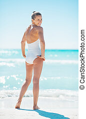 Full length portrait of young woman standing on beach