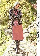 Full Length Portrait Of Young Woman Walking In Autumn Garden