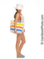 Full length portrait of young woman with beach bag