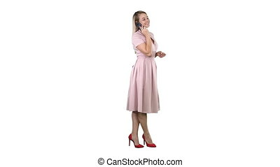 Pretty girl in pink dress on the phone on white background.