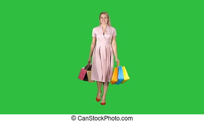 Shopping woman holding shopping walking to the camera on a Green Screen, Chroma Key.