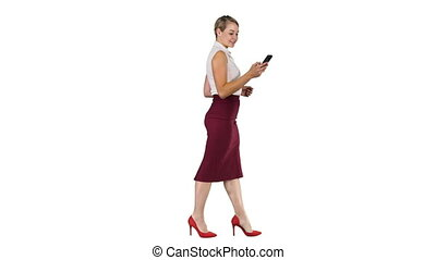 Beautiful young woman is using an app in her smartphone device to send a text message and walking on white background.