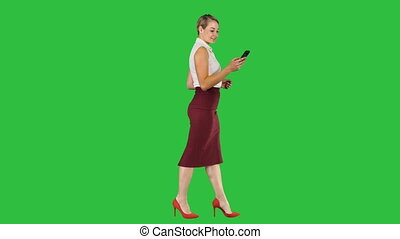Beautiful young woman is using an app in her smartphone device to send a text message and walking on a Green Screen, Chroma Key.