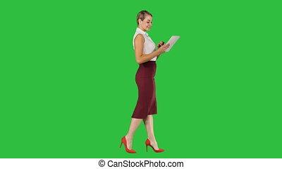 Businesswoman using electronic tab walking on a Green Screen, Chroma Key.