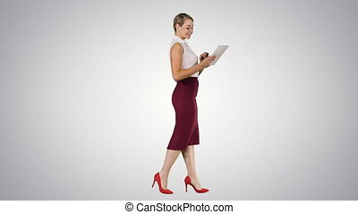 Businesswoman using electronic tab walking on gradient background.
