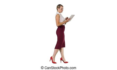 Businesswoman using electronic tab walking on white background.