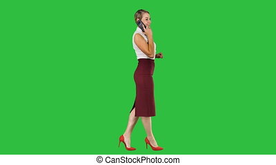 Businesswoman walking and making a call on a Green Screen, Chroma Key.
