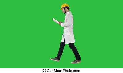 Engineer manager walking with hard hat is holding paper and checking on a Green Screen, Chroma Key.