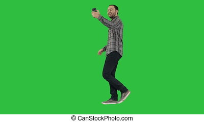 Happy smiling walking handsome bearded young man making selfie on a Green Screen, Chroma Key.