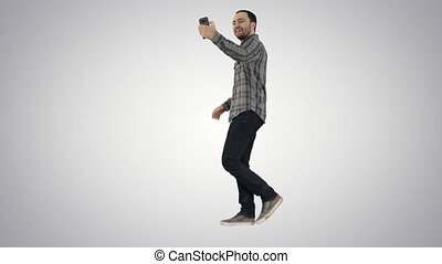 Happy smiling walking handsome bearded young man making selfie on gradient background.