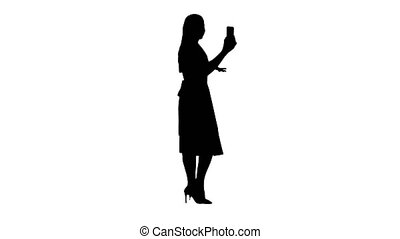 Silhouette Young woman in pink holding using smart phone recording video blog while walking.