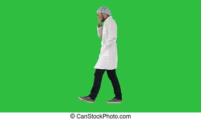 Thoughtful male doctor walking on a Green Screen, Chroma Key.