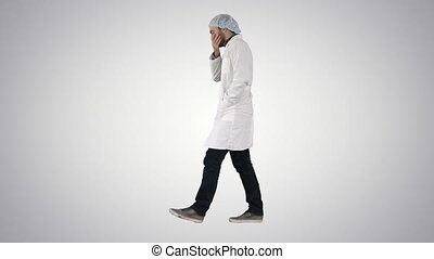Thoughtful male doctor walking on gradient background.