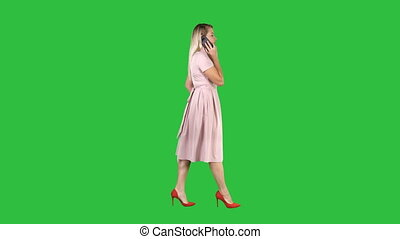 Woman in pink dress talking on the phone on a Green Screen, Chroma Key.
