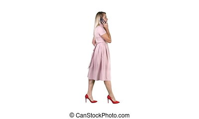 Woman in pink dress talking on the phone on white background.