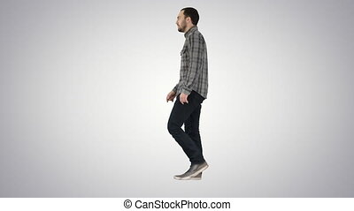 Young casual man walking on gradient background. - Full...