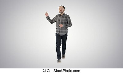Walking man pointing and explaining something on gradient...