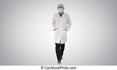 Walking young male doctor wearing surgical mask on gradient...