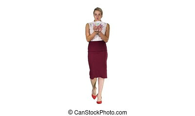 Woman counting money walking to the camera on white background.