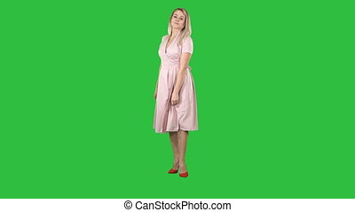 Woman in a pink dress making a turn and looks at her self like in the mirror on a Green Screen, Chroma Key.
