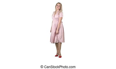 Woman in a pink dress making a turn and looks at her self like in the mirror on white background.