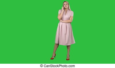Woman in dress smiling and talking on smartphone on a Green Screen, Chroma Key.