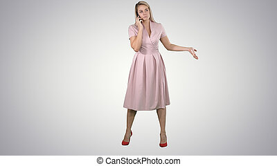 Woman in dress smiling and talking on smartphone on gradient background.